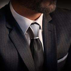Noeud de cravate en titane élégant et design. Costume anthracite, cravate noire et bijoux de cravate gris. Un mariage classe et contemporain