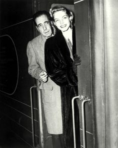 Humphrey Bogart and Lauren Bacall lean out of a railway car and smile, 1947.