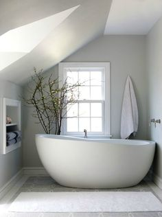 Zen bathroom with modern freestanding bathtub accented with wall-mounted tub filler next to towel niche filled with gray blue towels over gray marble mosaic tiled floor.