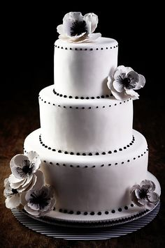A white three-tiered confection is elegantly decorated with black dots  and black and white sugar anemones.