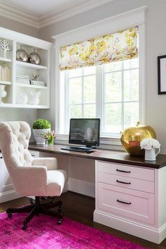 Chic home office features a built in desk adorned with bronze pulls accented with a beveled wood paired with a cream tufted rolling chair placed under windows dressed in a yellow floral roman shade alongside a hot pink overdyed rug.