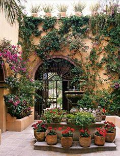 Geraniums in terracotta pots, arched doorway, wrought iron gate/door, fountain/water feature.