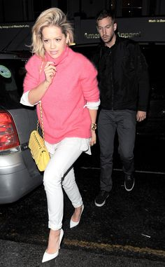 Rita Ora adds pops of color to her white ensemble with a pink cashmere sweater and a yellow quilted Chanel bag.