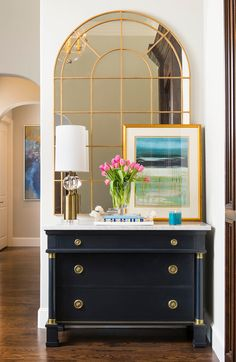 classic entry with dark blue console with marble top, gold mirror with oval arch, white and gold lamp and leaning art with gold frame
