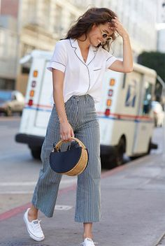 A Month's Worth Of Chic Spring Outfits: Woman wearing a pajama blouse, stripe culottes, white converse sneakers, beige oval sunglasses and a navy straw bag. Spring outfits, casual outfits, fashion trends 2018, casual outfits, simple outfits, comfy outfits #fashion2018 #casualstyle #springstyle #streetstyle #ootd #minimaliststyle #fashionblogger #summerstyle