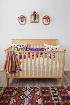 An eclectic, bright, colorful, and full of personality baby girls nursery. Modern folk art nursery design.