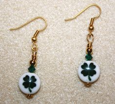 Handcrafted by Teal Palmetto, LLC.  Jolly lampwork beads with green shamrocks are the focals in this pair of St. Patrick's Day earrings.  An extra bit of bling is provided by the green Swarovski crystals that top each lampwork bead.  Each earring is also complemented with gold-tone accent beads.  The earrings hang from gold-tone fish hook ear wires.  Price: $15.