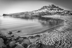 The view from the main beach at Lindos at sunrise. In black and white. Lindos. Rhodes. Greece. This picture was taken from the main beach looking towards the magnificent Acropolis. This picture was taken just after sunrise the only time the beach is completely deserted! #architecturalphotographer #buildingphotographer #commercialphotographer #constructionphotographer #constructionproductphotographer #freelancephotographer #industrialphotographer #interiorphotographer #landscapephotographer…