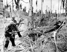 January 1943: Two American soldiers of the 32nd Division cautiously fire into a Japanese dugout before entering it for inspection during a drive on Buna, which resulted in a defeat of Japanese forces in the Papaun peninsula of New Guinea during World War II. (AP Photo/U.S. Army Signal Corps) #