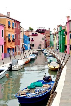 Brightly-colored homes in Burano lining the canal. A short ferry ride from Venice, Burano is a must-visit.