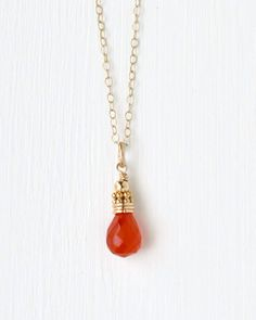 Add a small yet vibrant pop of color to your look. A faceted orange carnelian briolette is topped with a stack of smooth and textured gold filled and vermeil beads and is suspended from a delicate chain. Handcrafted gemstone jewelry by Blue Room Gems.
