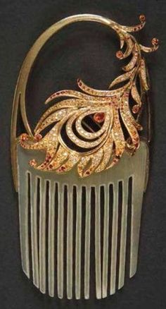 Horn comb with a gold shaft and jeweled phoenix feather. The decoration can be taken off the comb and worn as a brooch. The feather sports  yellow sapphires, mandarin garnets, diamonds and receives pearl-shaped fire opal in the middle. The comb comes in its original box and is signed Lalique. c. 1902.