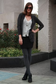 Short black skirt and long grey sweater.