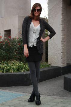 Short black skirt and long grey sweater.