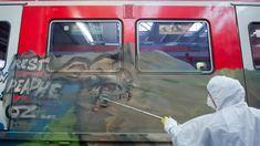 Ein Mitarbeiter reinigt in Ohlsdorf einen mit Graffiti besprühten Waggon