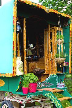 entree d'une roulotte très décorée avec du bois sculpté et des pots de plantes