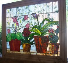 Large stained glass panel depicting potted plants on a window shelf