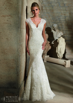 Lace v-neck fit and flare wedding dress with stunning cap sleeves and wide lace hem. Also has a beautiful sheer and lace back.
