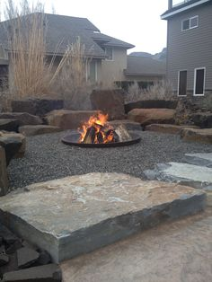 Rock Placing Company sells crusher cone fire pits that can be installed with various types of natural sitting rocks that make a very cozy and entertaining area for the whole family – perfect for spring, summer and fall evenings. Fire Pit And Pond, Fire Pit With Rocks, Fire Pit Area, Fire Pit Backyard, Backyard Patio, Rock Fire Pits, Camping Fire Pit, Camp Fire, Fire Pit Landscaping