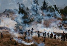 Nasser Ishtayeh    Palestinian demonstrators run from tear gas canisters fired by Israeli troops.