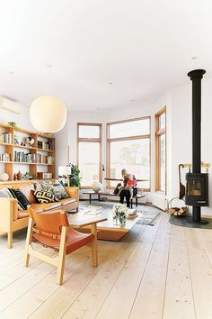 Airy open living room with so many good things: bay windows, wood floors, wood stove, midcentury leather.