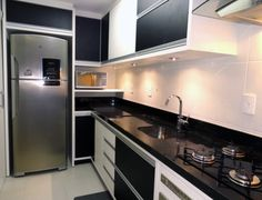 Mesmo com uma área estreita, o escritório Frente Verso Arquitetura conseguiu acomodar tudo nesta cozinha: a parede menor abriga a geladeira e o forninho. Os armários em preto e branco criam um bom efeito visual.