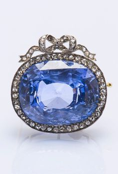 Auguste Frederik HOLLMING - An antique 14k gold, silver, Ceylon sapphire and diamond brooch, late 19th century. Features a natural Ceylon sapphire weighing approximately 28.19 carats. With maker's mark AH for Auguste Hollming, head of Fabergé workshop in 1880. 2 x 2.2cm.