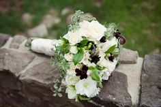 Dark maroon anchors a green and white bouquet