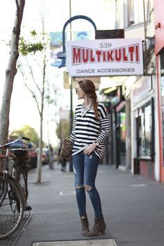 striped long sleeved shirt, distressed skinny jeans, tiger printed clutch, brown suede booties, statement necklace