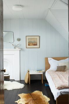 a peaceful, eclectic bedroom. Love the pale blue and white walls and fireplace with black painted floors