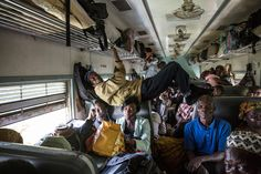 A man stretching across the second-class compartment, Lagos to Kano railway, Nigeria by Glenna Gordon