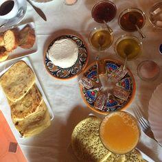 "Fresh local chèvre, orange juice, ""thousand holes"" bread, rghayif, pound cake and sweet rolls, yogurt, argan oil, and hot hot coffee."