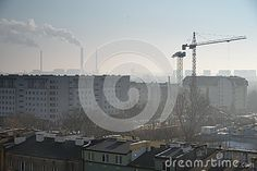 Warsaw in the winter morning viewed from the ninth floor. New built blocks of flats over the old ones. In front the construction site as well. In the back very bright sky with a view of the working factory.
