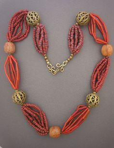 by Anne Holland |  Antique Venetian greenhearts (red on the outside with a green core), antique  tubular whitehearts (also know as Cornaline d'Aleppo beads), African amber  resin beads, and some old Ashanti brass beads combine to form a singular  and memorable wearable piece of art. Bronze hook and eye clasp |  Dorje Designs.  {495$}