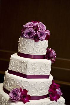 Purple roses accents on top of a four-tiered white fondant cake with piped designs and purple ribbon | villasiena.cc
