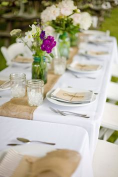 burlap table runner. mason jars with wild flowers. tied goodies at the place setting.