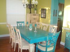Teal table and off white chairs. .. splash of green on the walls.