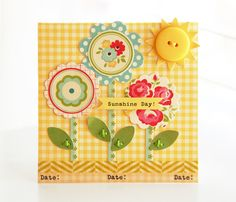 handmade card ... Sunshine day ... yellow button on top of sunrays ... three fantasy flowers ...punch circles and scalloped circles of various sizes from patterned paper ... layer them ... add a paper stem and leaves ... luv the cheerful papers on this card ... yellow gingham print background ...luv the hand sewn/made look ... strip of washi tape too ... luv it!!!