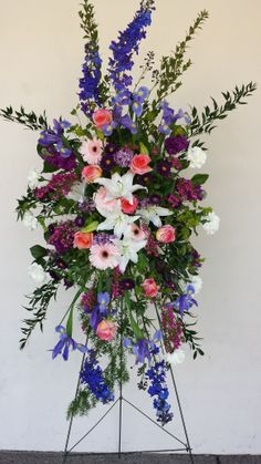 Standing Funeral Spray:  White lilies, Pink roses, Blue Delphinium, Purple Larkspur, Pink Gerbera Daisies, Purple Matsomato Aster and Boronia.