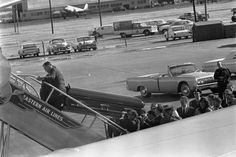 White House Photographer Cecil Stoughton records the moments when President Kennedy's casket is loaded onto Air Force One at Love Field in Dallas, Texas on November 22nd, 1963. Mrs. Kennedy is in the lower right corner of the frame.