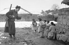 한국 G'day, 1951  ID 번호 : P01813.538의  메이커 : 로버트슨, 이안  한국  개인 (코리아) 크리스 벨 챔버, 스나이퍼 절, 3 대대, 왕립 호주 연대 (3RAR)의 일원, 미소 파도에 그들의 마을이 적군을 없애고 은신처에서 떠난 한 집단의 한국 어린이들. 눈은 땅에 있고 마을의 집 지붕에있다. Pte Bell-Chambers가 어깨에 메고있는 라이플은 .303 인치의 Short Magazine Lee Enfield (SMLE) No.1 MkIII * (HT)입니다.