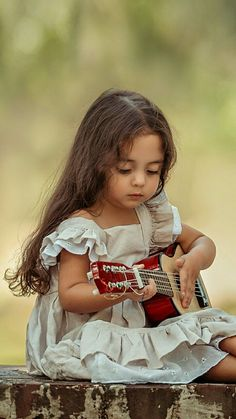 Little girl with her little guitar (six strings). When I was about this size, I learned to play my Mom's ukulele (4 strings).