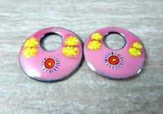Colorful floral enameled copper earrings charms.  22 mm Pink Yellow Purple  I made the enamel charms by fusing layers of powered glass to copper with my torch. The off set washer charms are pink with splashes of darker pink along with murrini and yellow flowers. The backs are counter-enameled for strength and durability. Please do not pierce, bend or cut the charms. Enamel is glass and will crack and break away from the copper.  Please note that these are not finished earrings. They are…