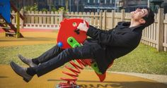 Young man reliving his childhood plying in a children's playground riding on a colorful red spring seat with a happy smile in an urban park Immature Adults, Fusion 360, How To Show Love, Coping Skills, Young Man, College Students, Playground, Novels, Childhood