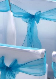 Turquoise sashes against crisp white chair covers