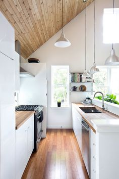 Wooden bench tops, set in sinks, window with sill for plants, pendant lighting. sloping ceiling with t+g panelling