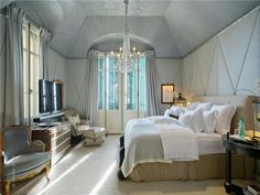 Vintage accents, fabric wall panels, and a mostly monochromatic, icy blue color palette give the bedroom a rich, serene feel. Source: Sotheby's