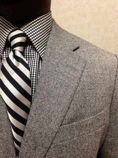 Striped tie and Checkered shirt beneath an elegant grey jacket.