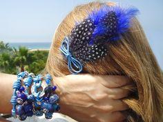 Pulseras con gemas y cordón de cuero, en color azul y, entrepiezas con baño de plata. Tocado de boda y fiesta, a juego, con plumas de guinea azules y lazo de cuero.