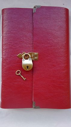 """Diário com mini cadeado e cantoneiras.  Couro sintético vermelho.  Costura longstitch  Forro interno em algodão cru.  Cantoneiras em ouro velho.  100 folhas papel reciclado sem pautas  Modelo igual da foto  CANTONEIRAS CONFORME DISPONIBILIDADE DE MODELO.   Aceito encomendas em outras cores (VER EM """"MOSTRUÁRIO"""").    PODE HAVER ALTERAÇÃO NA COR, DEVIDO LOTE E COR DE SEU MONITOR. R$ 70,00"""